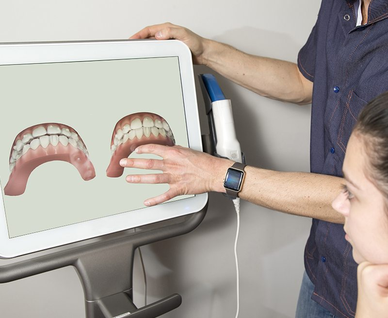 Dentist and patient looking at smile images on chairside computer