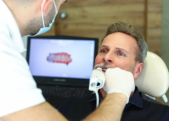 Dentist capturing images of patient's smile using 3D iTero scanner