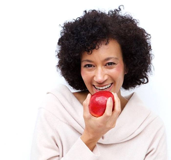 woman biting into red apple with dental implants in Grand Prairie