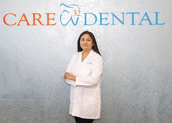 Doctor Desai in front of Care 32 Dental of Grand Prairie sign