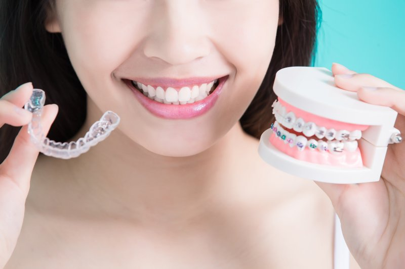 Patient holding up model of braces and Invisalign aligner